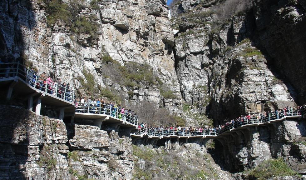 """所谓栈道,原指沿悬崖峭壁修建的一种道路。古时主要是为了物品运输,而旅游景区修建栈道,则是为了让游客看到常人不能到达的精华景点。 在十渡数百米高的陡峭悬崖上,长长的透明玻璃栈道,下面就是拒马河,你敢挑战吗? 玻璃栈道上,游客们表情各异,有尖叫的,有大笑的,有表情僵硬的,但每一个人都玩得不亦乐乎。一些游客因为看了网络上热传的""""玻璃栈道扶墙族""""照片,还特别模仿""""扶墙族""""的姿势留影,不亦乐乎。 十渡玻璃栈道安全吗?玻璃栈道为混凝土框架结构,3."""